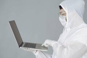 person in personal protective equipment using laptop to view electronic medical record